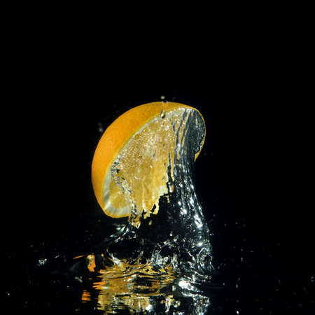 orange splashing out of water on black background photo