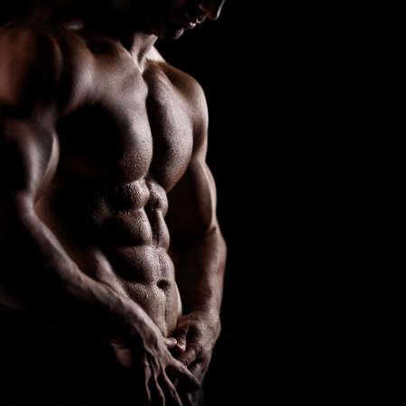 hombres musculosos: hombre atl�tico fuerte en fondo negro Foto de archivo