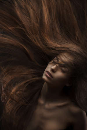 beautiful woman with long hair on dark background photo