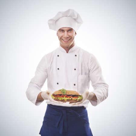 plato del buen comer: Chef sosteniendo un sándwich grande