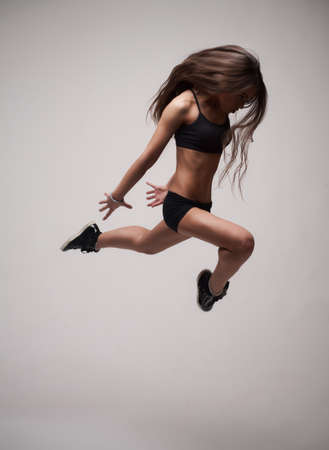 girl doing gymnastick jump photo