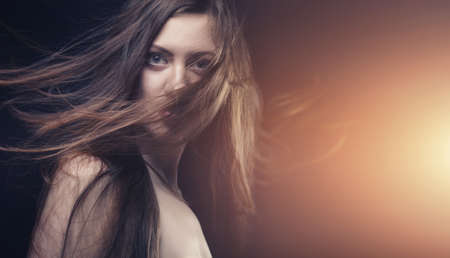hair dresser: young brunette woman with long flying hair
