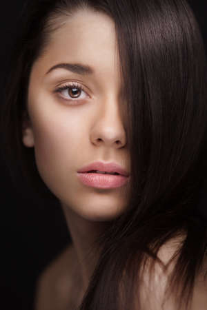 skintone: close up of a woman with hair over half her face Stock Photo