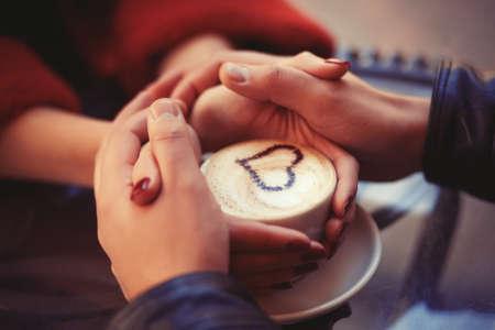 desayuno romantico: Cuatro manos alrededor de una taza Foto de archivo