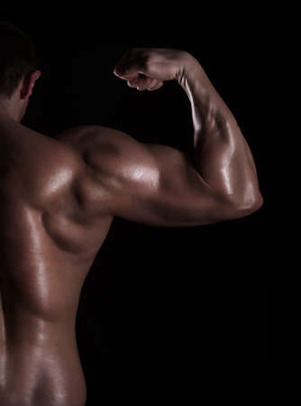 back muscles: back view of a muscular man showing his biceps