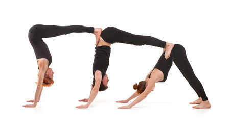 Two women and one men practicing yoga photo