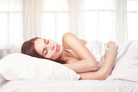 woman sleep: Beautiful woman lying down in bed Stock Photo