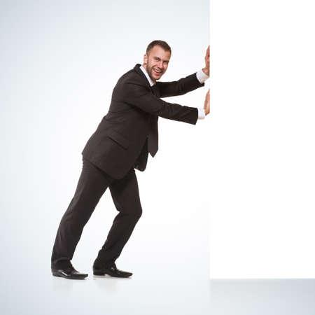 Businessman pushing away something Standard-Bild