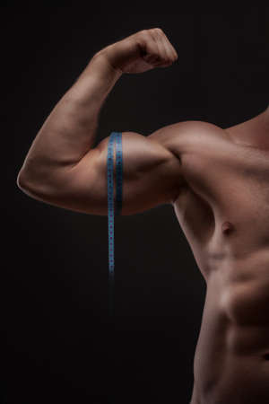 man measures his biceps with measuring tape photo