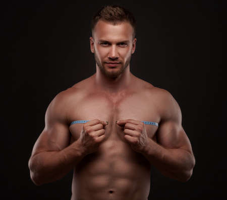 Muscular man use measurement tape photo