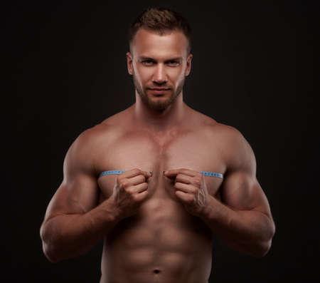measurement tape: Muscular man use measurement tape Stock Photo