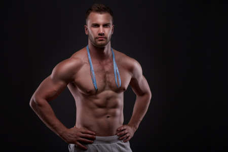 male torso: Muscular man with measurement tape Stock Photo
