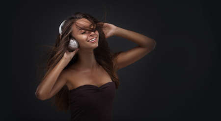 Beautiful woman with a headphones on dark studio background photo