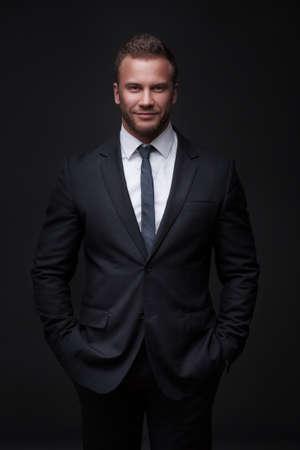 Portrait of young businessman isolated on dark background Standard-Bild