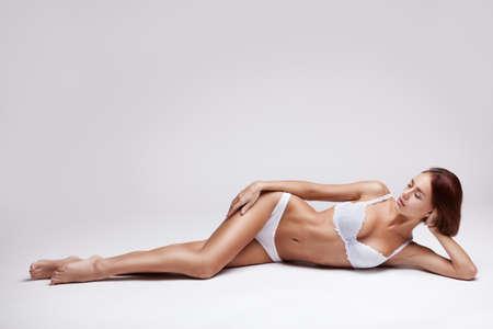 nias en bikini: hermosa joven en ropa interior blanca que miente sobre un fondo claro Foto de archivo