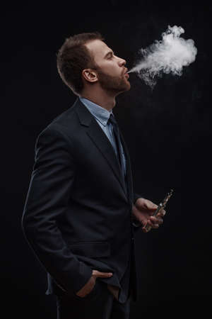depressed man: young business man blowing smoke of electronic cigarette on dark background