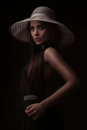 magnificent vintage style woman in a hat over dark bakground photo