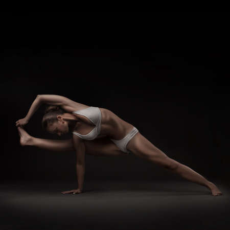 studio shoot of healthy latino woman doing yoga isolated photo
