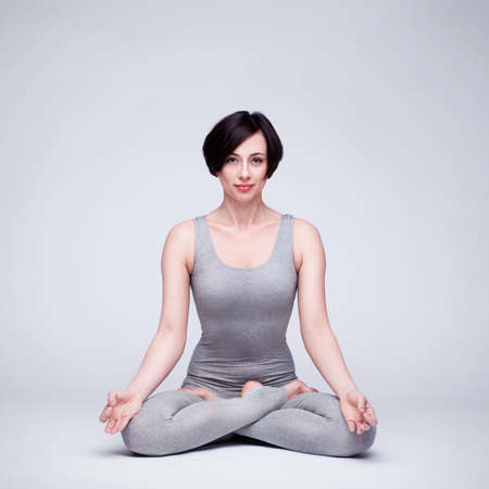 young beautiful woman yoga posing on a gray studio background photo