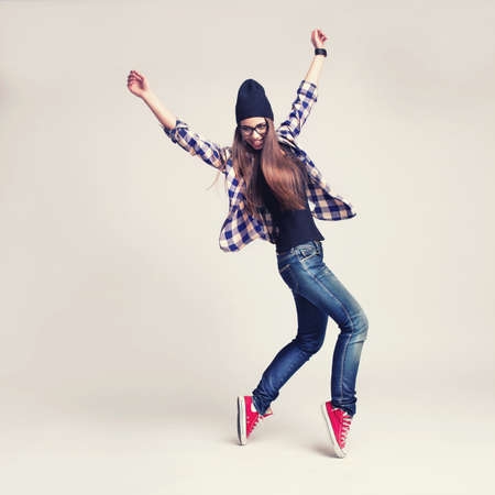 Dancing hipster girl in glasses and black beanie on light background