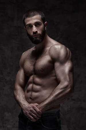 strong athletic beardy man on dark grey background