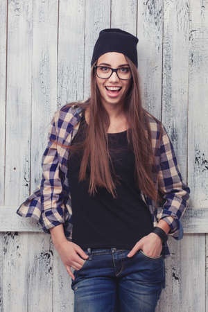 Hipster girl in glasses and black beanie on the wooden background