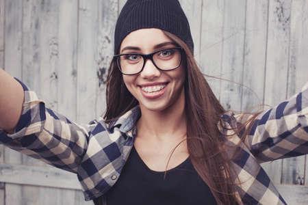dívka: Hipster dívka v brýle a rovnátka dělat selfshoot