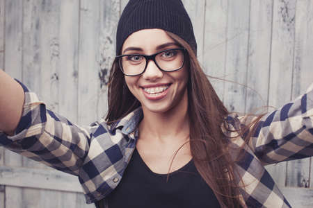 cute braces: Hipster girl in glasses and braces making a selfshoot
