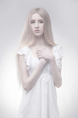 fairy blond girl in glowing light on grey gradient background photo