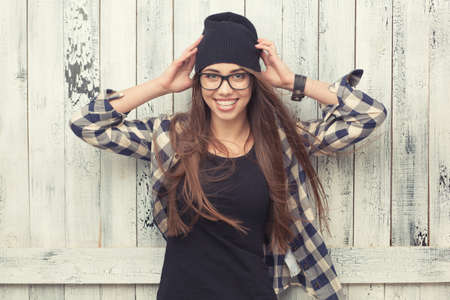 Smiling hipster girl in glasses and black beanie on the wooden background