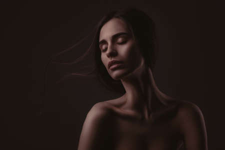 lowkey: lowkey portrait of beautiful woman with closed eyes over dark background Stock Photo