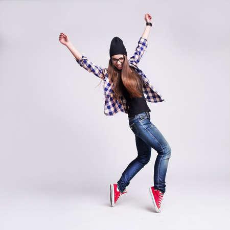 Dansend hipster meisje in glazen en zwarte muts op de houten achtergrond Stockfoto