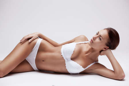 femme en sous vetements: belle jeune fille en lingerie blanche couché sur un fond clair