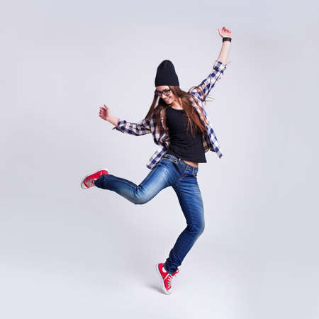 Dancing hipster girl in glasses and black beanie on the light grey background