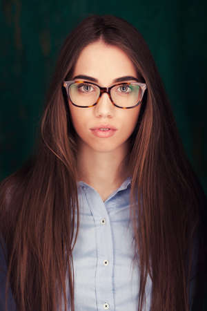 Close-up portrait of beautiful young woman in glasses on dark green background