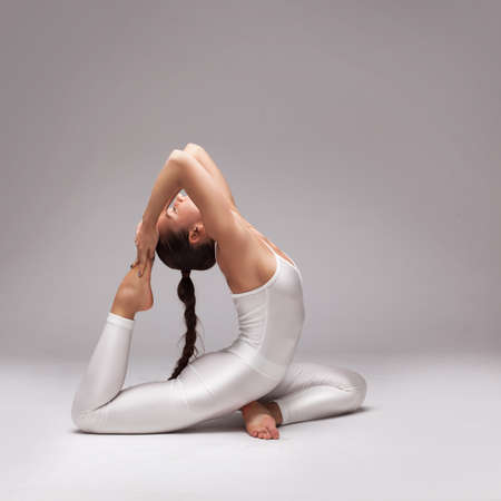 young beautiful woman yoga posing on grey gradient studio background photo