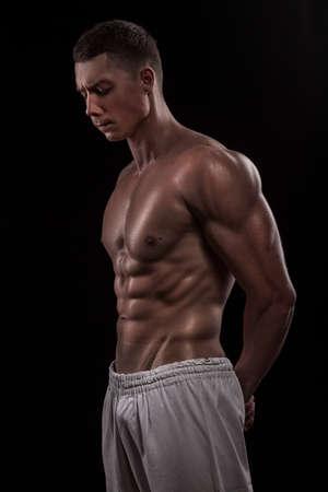 cuerpos desnudos: hombre joven atleta fisicoculturista aislado sobre fondo negro