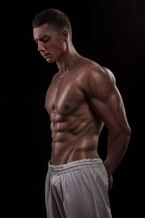 naked young people: young athlete bodybuilder man isolated over black background