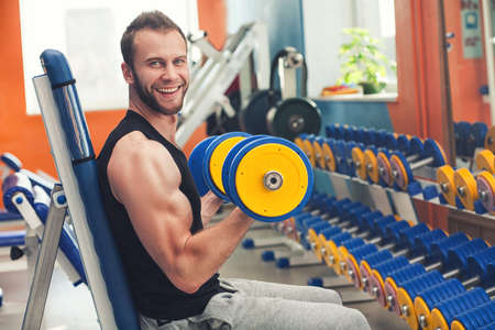 pesas: Pesos de elevación del atleta sonriente joven en el gimnasio