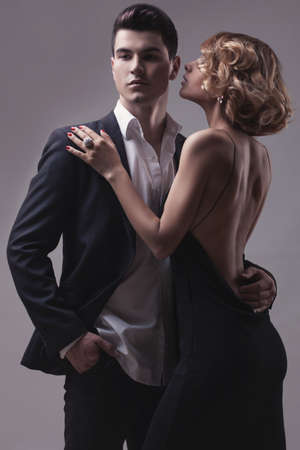 Well-dressed retro couple over grey studio background