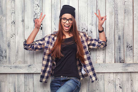 Hipster girl in glasses and black beanie show victory sign on the wooden background