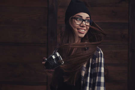 Hipster smiling girl in glasses and black beanie with vintage camera on the wooden background