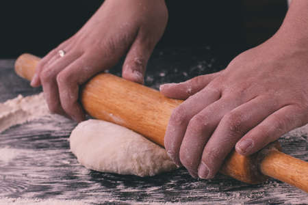 rollingpin: Close up homemade cooking, female hands roll out pastry with rolling-pin on wooden table