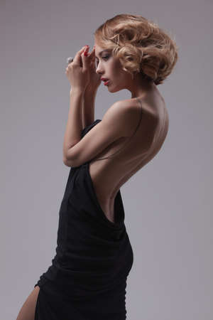 mooie vrouw model poseren in een elegante jurk op de grijze achtergrond studio