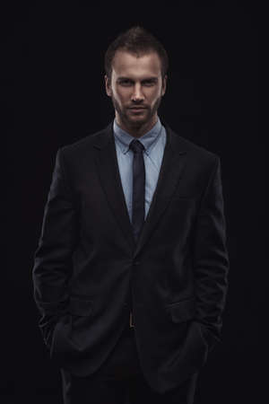 Portrait of young businessman isolated on dark background 스톡 콘텐츠