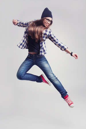 Dancing hipster girl in glasses and black beanie on the wooden background