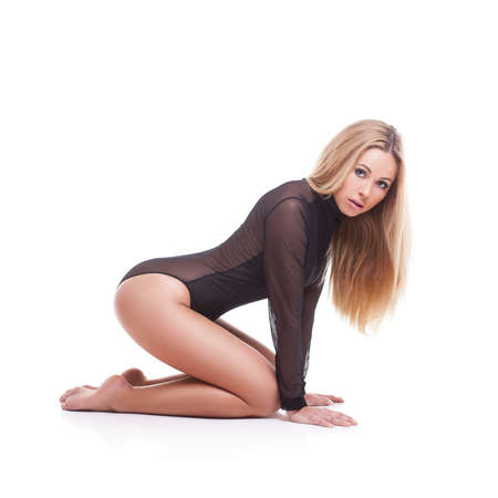 Sensual blond woman with long hair in black underwear sitting on white studio background
