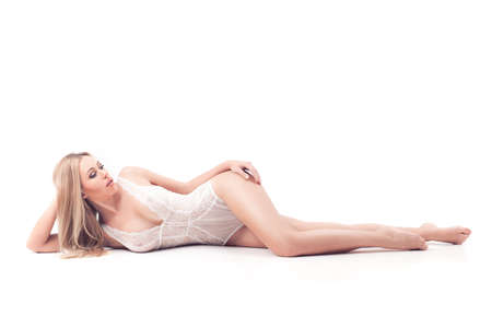 Sensual blond woman with long hair in white underwear lying on white studio background