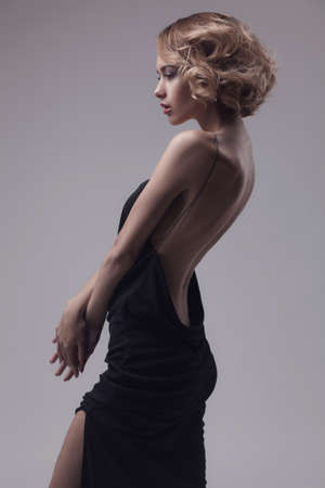 beautiful woman model posing in elegant dress on the grey studio background Stockfoto