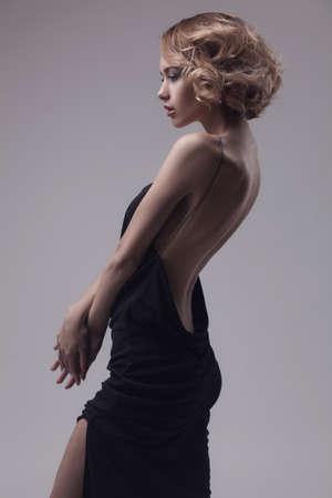 beautiful woman model posing in elegant dress on the grey studio background Standard-Bild